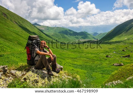 Young tourist resting on the top overlooking the valley