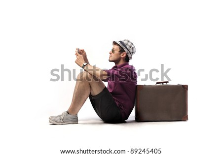 Young tourist sitting against a suitcase and using a mobile phone - stock photo
