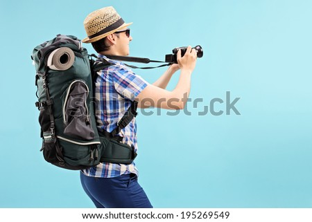 Young tourist taking a picture with camera on blue background