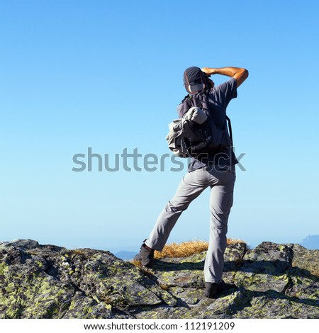 Young tourist taking photos outdoor from the top of the mountains - stock photo