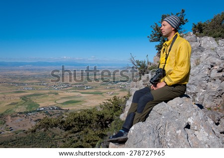 Young tourist with a camera resting on the top overlooking the valley - stock photo
