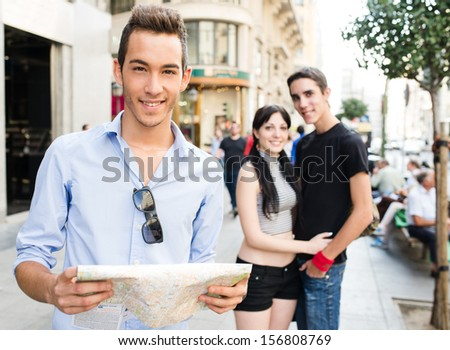 Young tourist with a map and with two friends
