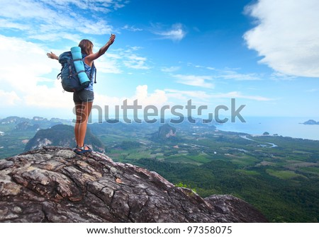 Young tourist with backpack enjoying valley view from top of a mountain - stock photo
