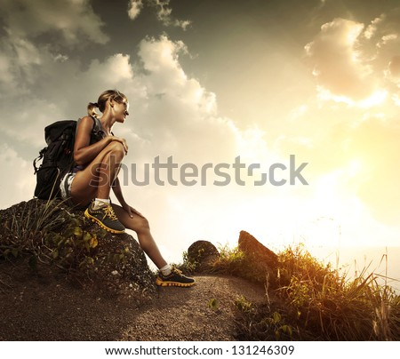 Young tourist with backpack relaxing on rock and enjoying sunset - stock photo