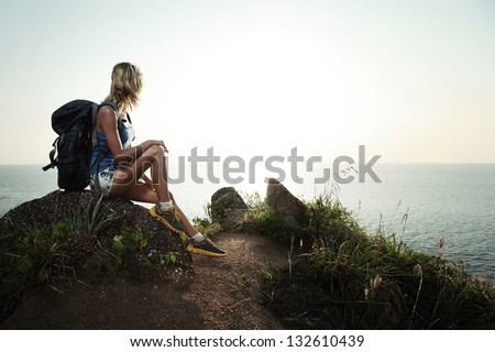 Young tourist with backpack sitting on a rock and enjoying sunset - stock photo