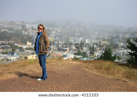 Young tourist woman enjoying scenic view outdoors ontop of the Kite Hill in San Francisco, California, USA. - stock photo