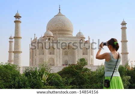 Young tourist woman taking picture of Taj Mahal - stock photo