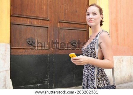 Young tourist woman visiting a characterful destination city street, using a smart phone while walking a street with a large wooden door on a summer holiday, outdoors. Travel technology lifestyle.