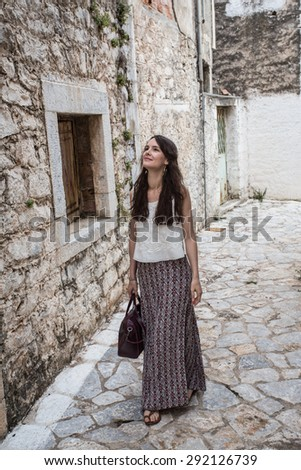 Young tourist woman visiting a picturesque destination city street, contemplating the architecture  on a summer holiday, outdoors. Travel lifestyle weekend break. - stock photo