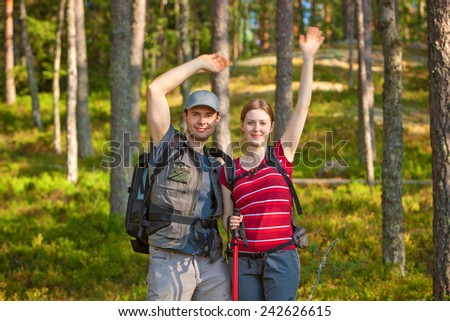 Young tourists couple waving hands and smiling in forest. - stock photo