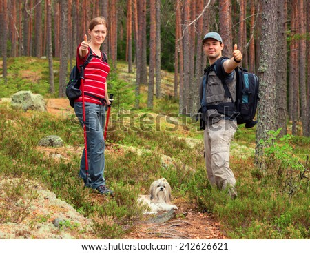 Young tourists couple with dog showing thumbs up on forest background. - stock photo