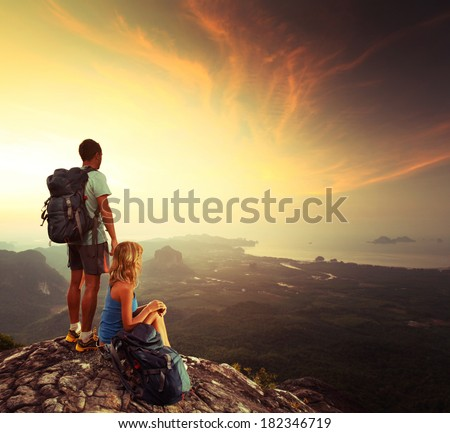 Young tourists enjoying sunrise on top of the mountain after trekking