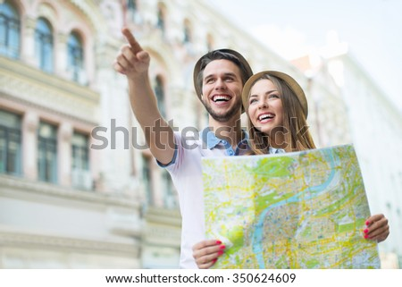 Young tourists with a map outdoors - stock photo