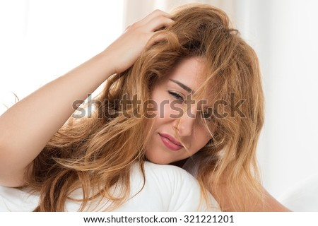 Young tousled woman waking up early in the morning  - stock photo