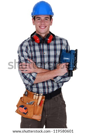 Young tradesman holding a sander - stock photo