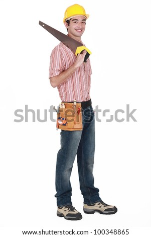 Young tradesman holding a saw - stock photo