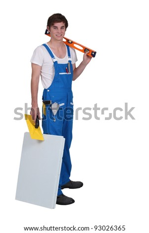 Young tradesman posing with his tools and materials - stock photo