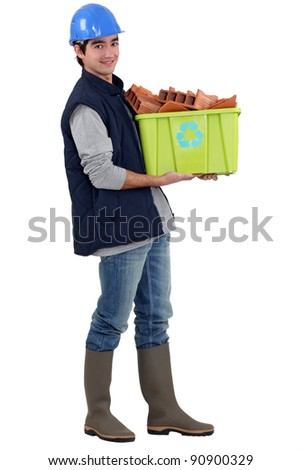 Young tradesman taking out the recycling - stock photo