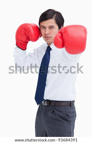 Young tradesman with boxing gloves striking against a white background