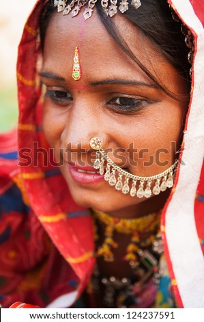 Young Traditional Indian woman in sari costume covered her head with veil, India