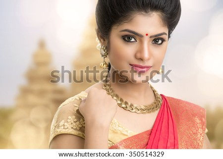 Young traditional Indian woman portrait on temple background.