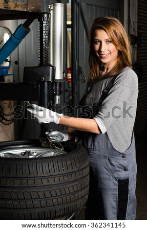 Young trainee changing  car tyre  - stock photo