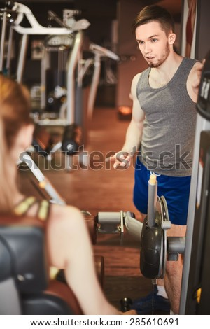 Young trainer consulting girl about exercising on facilities