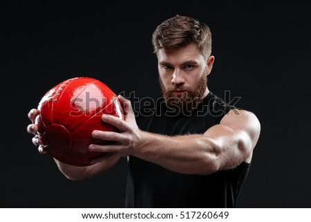 Young trainer with ball. shows the ball. holding ball in hands. isolated dark background