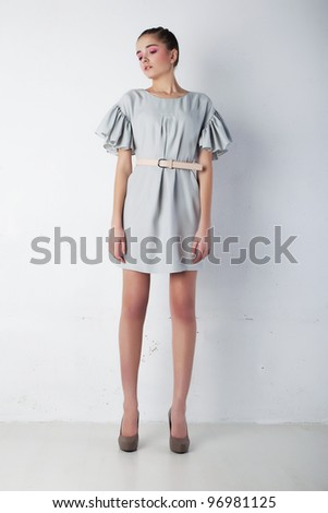 Young tranquil woman in light blue dress posing. Fashion style - stock photo