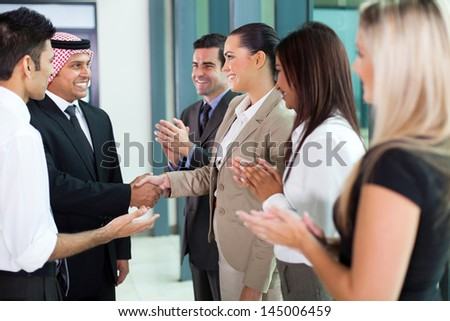young translator introducing arab businessman to group of businesspeople - stock photo