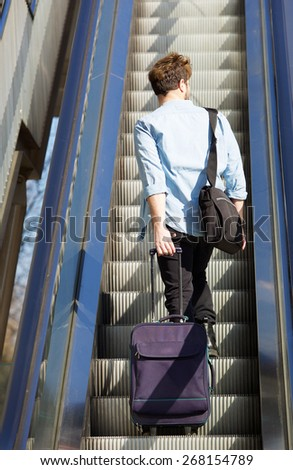 Young travel man standing on escalator with bags - stock photo