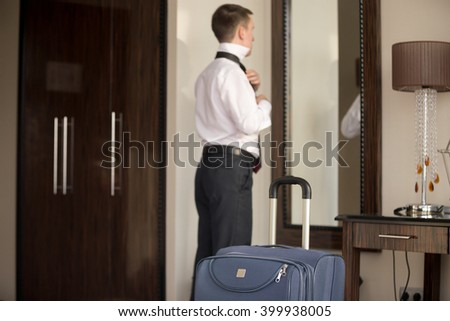 Young traveler businessman wearing white shirt standing at the mirror and getting dressed for meeting or work after arriving in the hotel room with his luggage. Focus on the suitcase - stock photo