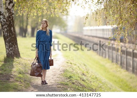 Young traveler in vintage blue dress leaves home for adventures.
