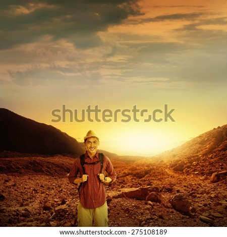 Young traveler male trekking on the papandayan mountain in Indonesia at summer time - stock photo