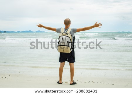Young traveler man with backpack walking alone at seaside. - stock photo