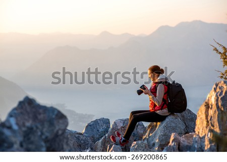 Young traveler photographer with photo camera and backpack sitting on the top of mountain and looking on the sunset - stock photo