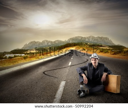 Young traveler sitting on a countryside road - stock photo