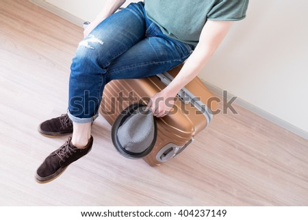 Young traveler sitting on big and heavy golden luggage for vacation in crossed legs pose with gray hat