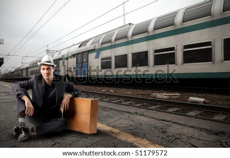 Young traveler sitting on the platform of a train station - stock photo
