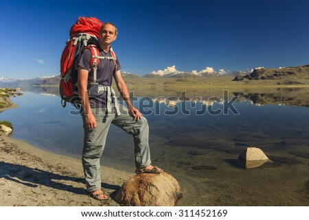 Young traveler with a backpack on the background of the lake and mountains.