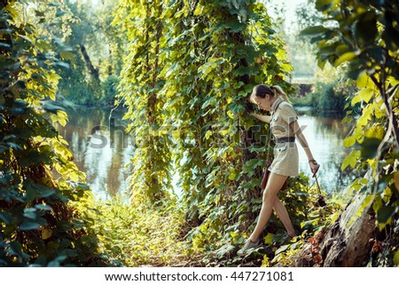 Young traveler with camera in the jungle. Discovery concept. Travel