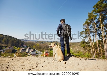 Young traveler with his dog on the hill - stock photo