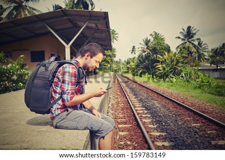 Young traveler with mobil phone in the railway - stock photo