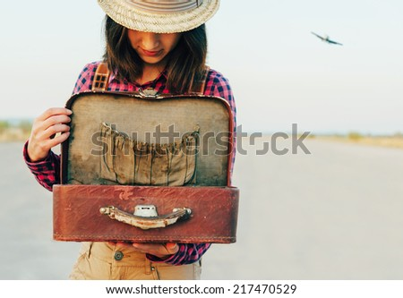Young traveler woman looking for something in the open vintage suitcase outdoor - stock photo
