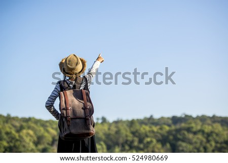Young traveler woman with a hat and bag standing on stone near a river bank
