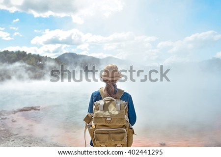 Young traveler woman with hat and bag in wai-o-tapu park near hot pool geyser. New Zealand - stock photo