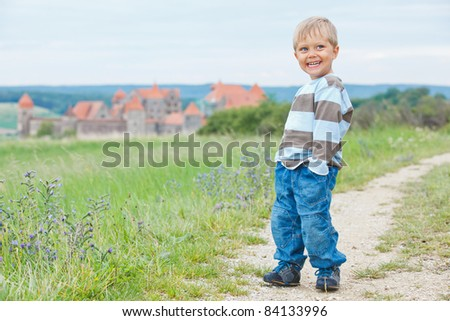 Young travelers. Cute little boy on a tour of European medieval castles. Vertical view - stock photo