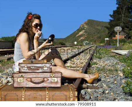Young traveling woman with her suitcases on the railway tracks - stock photo