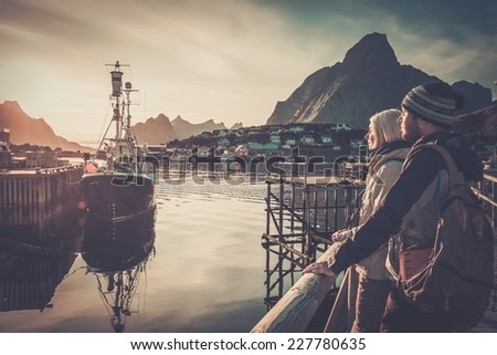 Young travellers couple looking at sunset in Reine village, Norway - stock photo
