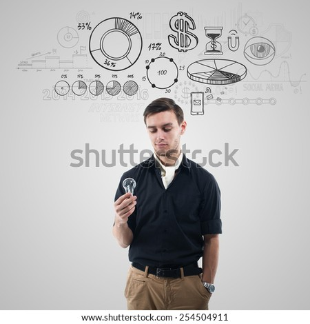 Young trendy businessman holding a buld and thinking about business, money, projects. - stock photo